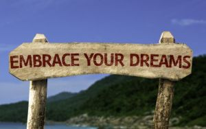 Embrace Your Dreams sign with a beach on background