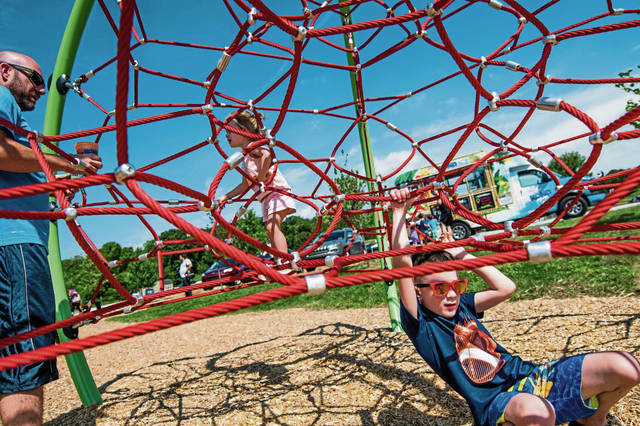 Jackson Richey, 4, slips underneath the new jungle gym playground equipment as his sister, Brynlee, 2,  and dad, Charlie of Penn Township enjoy a frozen shaved ice.                                 Parkgoers brace for water splashing out of the bucket fountain. The bucket works on a cycle and splashes out water after several minutes.