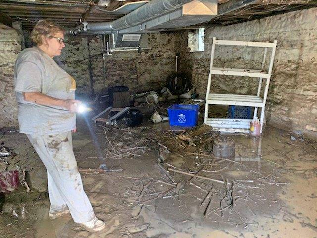 Janet Seman looks around in her mud-soaked basement after her home flooded the day before.