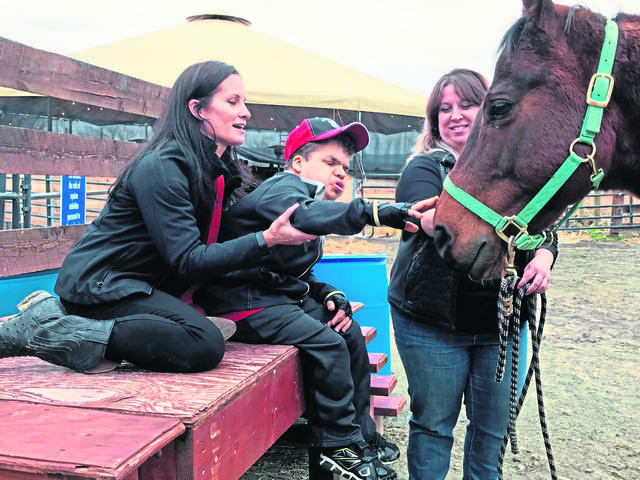 Catherine Markosky, left, helps her son, Mason, 18, pet therapy horse Rocky, held by licensed counselor Mandy Orvosh of Saltsburg, during an open house March 29, 2019, at Markosky's Ligonier Therapeutic Center in Cook Township. The roofed horse pen in the background was unveiled at the event. Mason, who benefits from equine therapy, has Costello Syndrome, a genetic disorder typified by short stature and developmental delays.