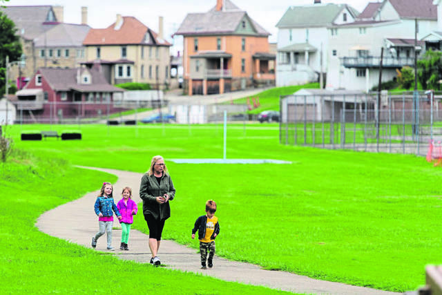 Sheila Jaskolski walks with Alexee Smith (left) and siblings Holdyn Schmidt and her brother Kane, along the path at Irwin Park.