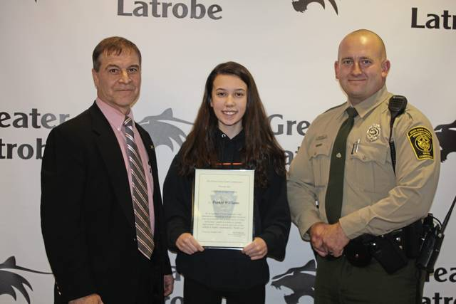 Greater Latrobe School District ninth-grader Parker Williams, center, receives a certificate of appreciation on Friday from Southwest Region Deputy State Game Warden Ken Williams, left, and Game Warden William Brehun, right, recognizing her effort to get help for a deer she saw caught in a fence on Nov. 4, 2019, in Unity Township.