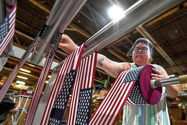 Cindy Hiles works at preparing small flags at Online Stores in New Stanton, which is one of the nation's largest suppliers of American flags.