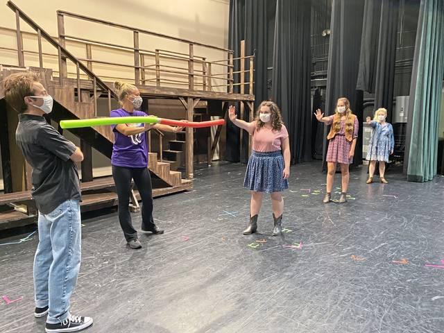 "Penn-Trafford Drama Guild choreographer Deborah Cuccaro uses pool noodles to properly social-distance Nick Konopka, Morgan Bruni, Madi Kerrigan and Maddy Petrillo during a rehearsal for ""Footloose."""