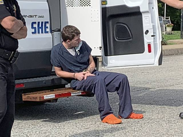 Nathan Quidetto waits outside the office of District Judge Mark Bilik on Friday. Homicide and related charges against him were held for court in connection with a fatal shooting in Derry Township.