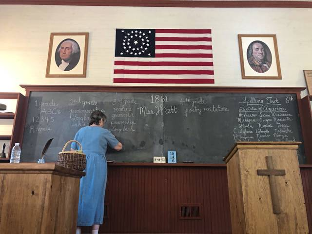 Suellen Watt writes lessons on the blackboard at the Murrysville schoolhouse replica on Wednesday, Aug. 5.
