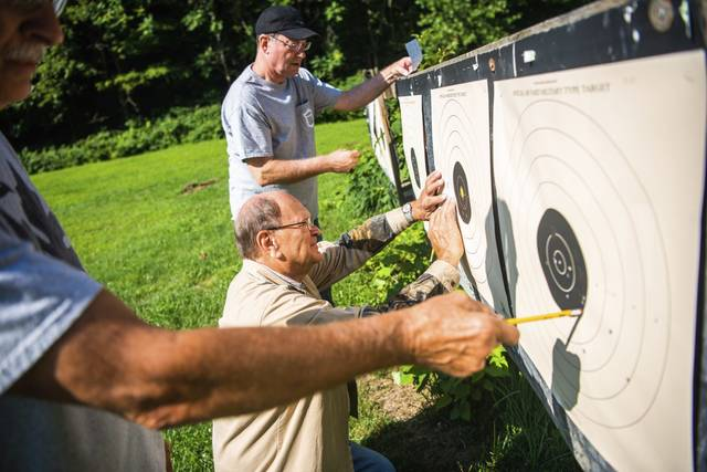 Jerry Berchok, center, of Elizabeth, Greg Cain, background, from South Hills, and Ron Murajda, left, from Rillton, mark score cards and compare groupings after competing in a round of the Civilian Marksmanship Program on Sunday at the White Oak Rod & Gun Club.