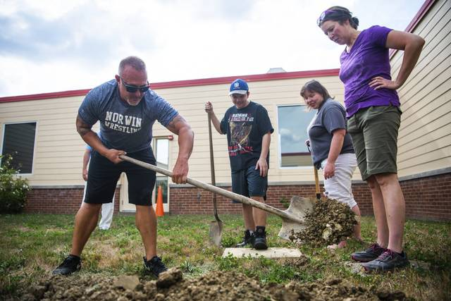 Jason Zugai, left, Ryan Griser, background, Beth Griser, right, and Keri Holton, far right, search for a buried time capsule on Wednesday<ins>,</ins><ins> Aug. 12, 2020</ins> in the courtyard of Adelphoi Village Academy in North Huntingdon.