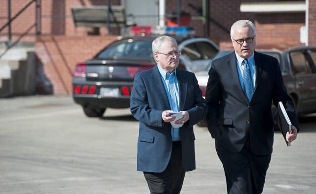 The Rev. Emil Stephen Payer (left) leaves an arraignment with his attorney Thomas Merrick on theft charges at the office of District Judge Charles Moore in Scottdale on Tuesday, March 11, 2014.