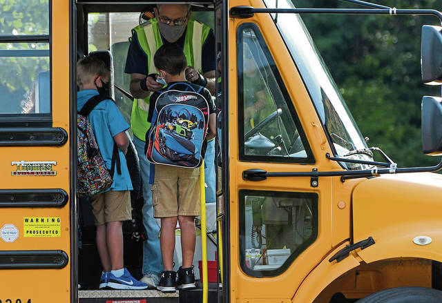 Norwin School District bus driver Frank Queen, 77, assists a student with his mask before he exits the bus at Hahntown Elementary School in North Huntingdon on Monday, the first day of school. Queen has been a bus driver for 25 years.