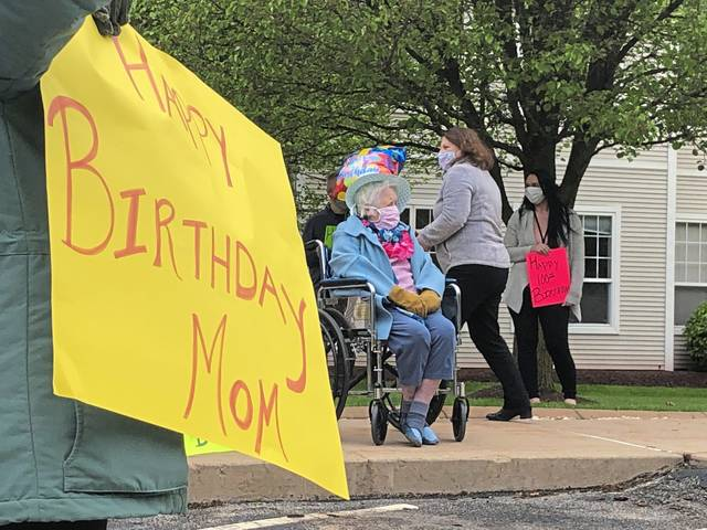 Sara Palone's daughter, Linda Roberts of Forest Hills, holds a birthday sign for her mother as fellow centenarian Sally Born sits outside at Redstone Highlands in Murrysville in May.