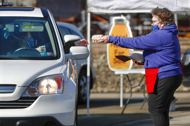 A patron wearing a protective mask, left, makes a purchase of baked goods from her vehicle at the Greensburg Farmers' Market opening day, Saturday, April 25, 2020, in Greensburg.