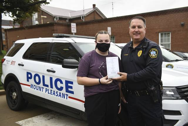 Arianna Cholock, 12, poses for a photo with Mt. Pleasant police Chief George Grippo outside the station on Friday. Cholock made candy bags to deliver to local police departments, including Mt. Pleasant, as a fun way to show support to officers.