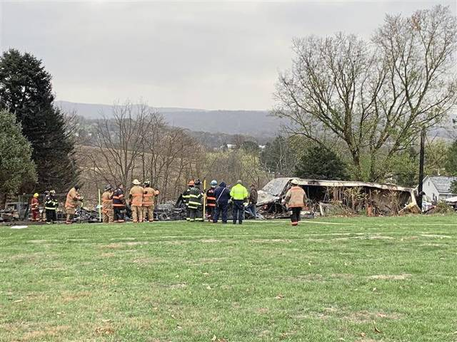 Firefighters surround the remains of a trailer destroyed by fire in Mt. Pleasant Township Monday.