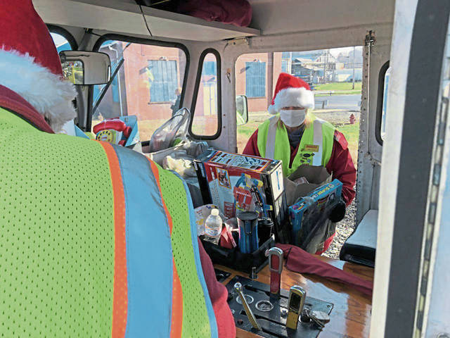 Brian Davis (back to camera) and his wife, Jane, of Ravenna, Ohio, fill their railcar with gifts donated for the Marine Toys for Tots program at its stop in Scottdale on Saturday.