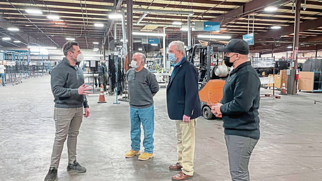FlexScreen CEO Joe Altieri (from right), Murrysville Mayor Regis Synan and Export Mayor Joe Zaccagnini talk to a FlexScreen employee Feb. 3 during a tour of the Murrysville facility.