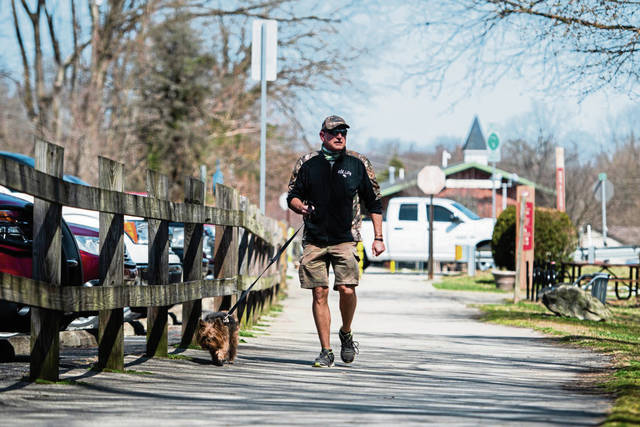 David Anderson of Collinsburg walks his Yorkie dog, Geno, on the Yough River Trail portion of the Great Allegheny Passage trail on March 22 in West Newton.
