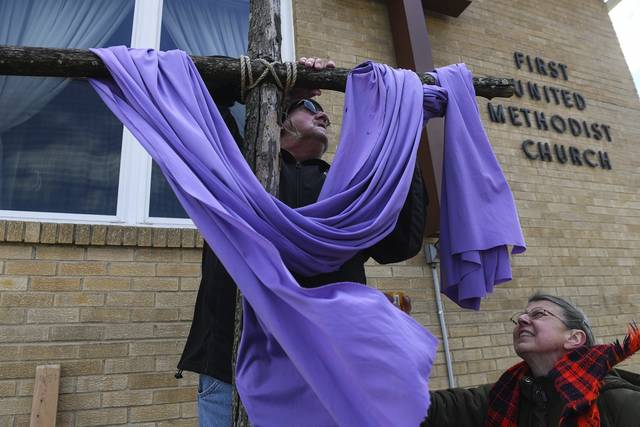 Jim Shawley (left) undrapes a cross as the Rev. Lola Turnbull of Derry First United Methodist Church looks on as they present The Way of the Cross during a Good Friday Cross Walk in Derry.