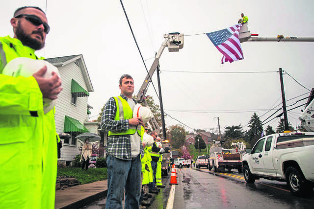 West Penn Power utility trucks make their way through Main Street in Madison during a funeral procession for West Penn Power lead lineman Dillon Walton on Thursday, Oct. 29, 2020 outside Beatty-Rich Funeral Home in Madison, as linemen with West Penn Power, including Nash Harbaugh, a co-worker of Walton's, pay their respects.