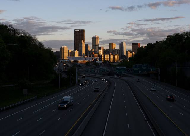 The sun sets on Downtown Pittsburgh as cars drive on Interstate 279.