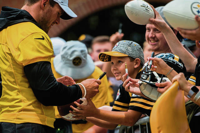 Young fans reach out to get signatures from T.J Watt on July 26, 2019, at Saint Vincent College as players make their way to the field for practice during Steelers training camp.