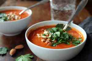 spicy tomato soup with red pepper, chili parsley leaves and chopped almonds