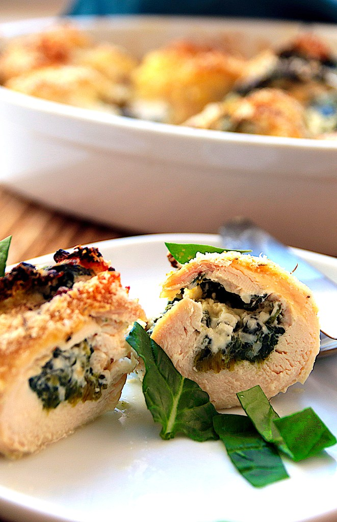 Baked chicken rolls filled with spinach and cream cheese, served on a white plate and sprinkled with basil leaves