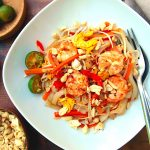 A white plate of pad thai with shirataki pasta, mixed with shrimp, carrots, bean sprouts and egg, sprinkled with peanuts and served with a lime