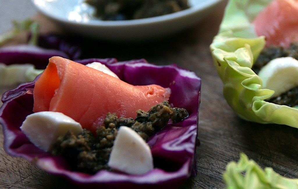 A red cabbage leaf topped with tapenade, mozzarella cubes and a slice of smoked salmon