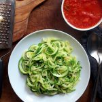low carb zucchini pasta with a bowl of tomato sauce and a chunk of parmesan cheese