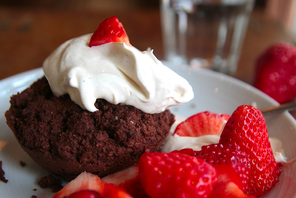 An almond cocoa mug cake served on a white plate, topped with whipped cream and strawberries