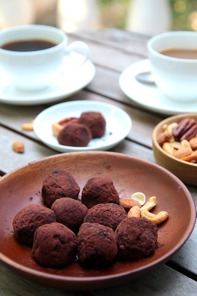 chocolate avocado balls in a wooden bowl, served with nuts - and two cups of coffee in the background