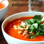 A bowl of tonato red bell pepper soup, topped with parsley leaves and chopped almonds
