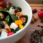 A white bowl of spinach salad with feta cubes, nutes and mango pieces served with a piece of seedy crispbread on a bamboo board