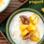 a green bowl with yogurt, topped with pineapple pieces and walnuts.