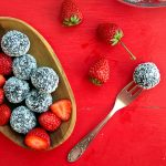 chocolate balls in a wooden bowl, placed on a red table, with a few strawberries