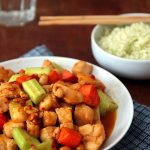 a plate of Kung Pao chicken with carrots, cucumbers and peanuts on a blue napkin, served with cauliflower rice