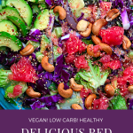 a flat turquiose bowl filled with red cabbage salad, slices of avocado, and sprinkled with roasted cashew nuts