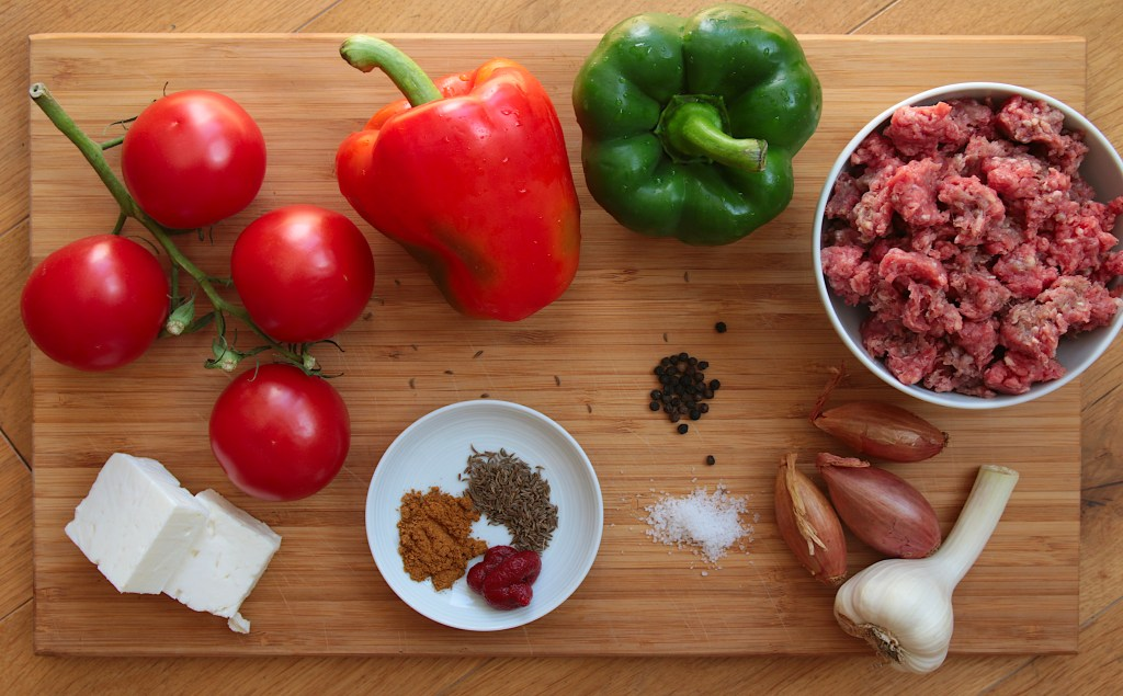 Tomatoes, bell peppers, feta cubes, a bowl of minced beef, and a few other ingredients placed on a bamboo chopping board