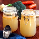 Three mason jars filled with home made vegetable stock on a dinner table, decorated with carrots, broccoli and other veg