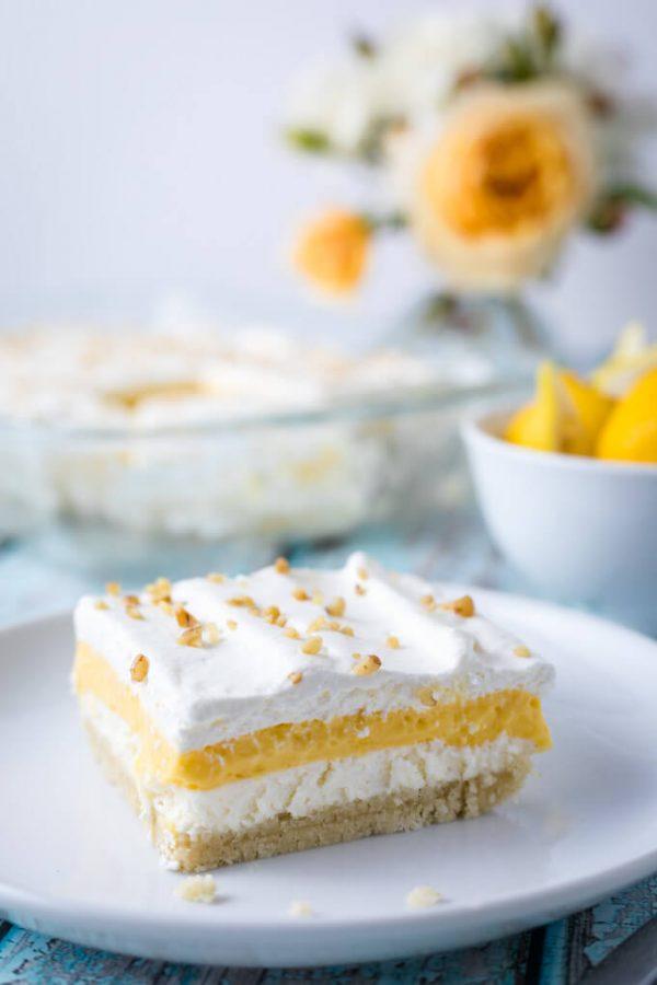 Lemon layered dessert with crumb base, cream cheese layer, lemon curd layer and whipped cream.