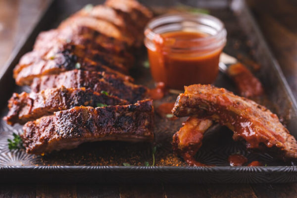 Baked and sliced pork ribs slathered with keto bbq sauce on a sheet pan