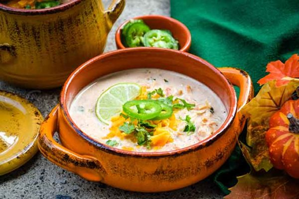 A bowl of low carb chicken taco soup with cheese, cilantro, and jalapeno garnish