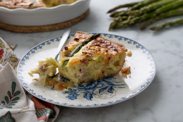 Slice of ham and asparagus quiche with fork on blue and white floral plate
