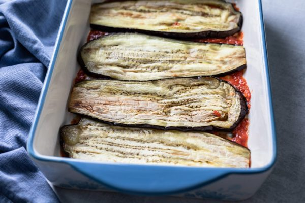 tomato sauce topped with sliced eggplant placed side-by-side in a lasagna pan