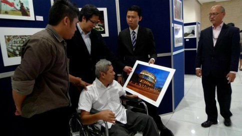 King Chai showing off one of Uncle Hatim's works from his days as a Petronas photograppher to Senator Gan