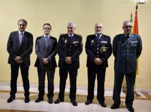 Fotografía donde pueden verse cinco hombres, dos con traje y tres con uniforme.