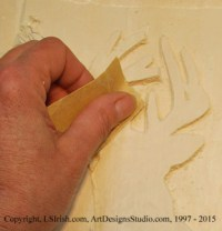 Using sandpaper on a relief wood carving