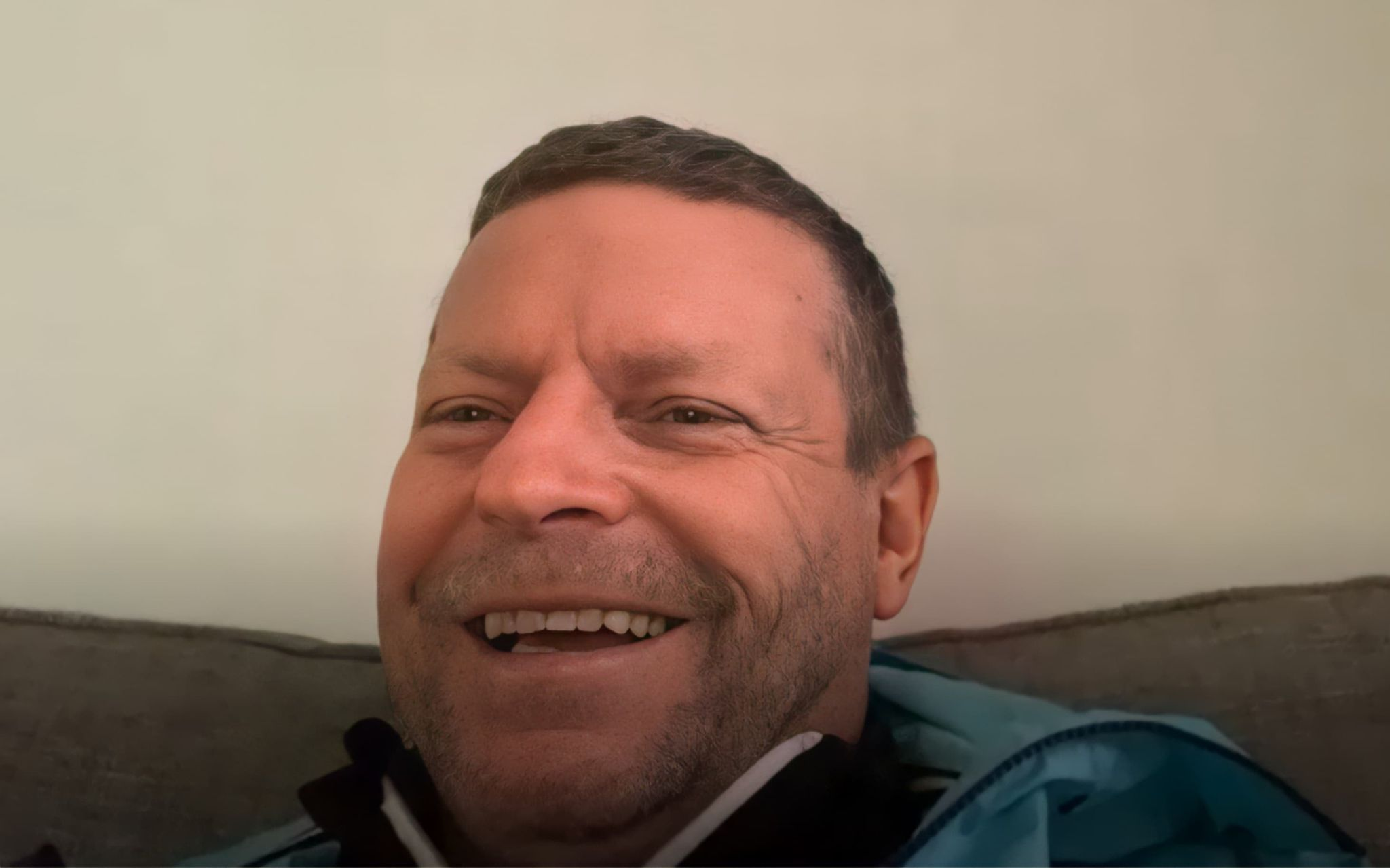 Micky Hazard, former Tottenham Hotspur player, talking about his efforts to stop loneliness over lockdown. He is wearing a blue windbreaker jacket, sitting in his living room, and smiling.