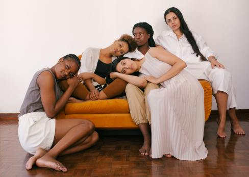 Image of a diverse group of people of people, sitting on an orange couch, leaning on each other, representing the healing that comes with finding a supportive community.